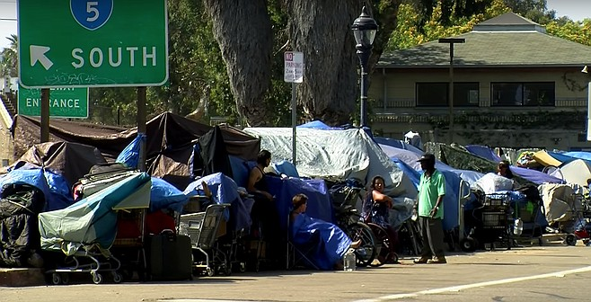 """President Trump said during his visit that he wants to 'help' the homeless in California by tearing down their tents and moving them into government housing,"" said Homeless Advocate James Hardknox. ""And it's true that there are those of us who have been agitating for increased government assistance in finding homes for these people. But when Donald Trump offers to help, it should be enough to give any decent person pause. And after pausing, I realized that Janis Joplin sang it best: 'Freedom's just another word for nothing left to lose.' Which means that when you've got nothing left to lose, you're truly free. And freedom is what America is all about. How dare Trump try to deny these people their freedom by taking away their chosen lifestyle and forcing them to live in some square - and I do mean square - building? And now Imperial Beach is prohibiting people from sleeping on city property, including sidewalks. Sleeping, like skateboarding, is not a crime!"""