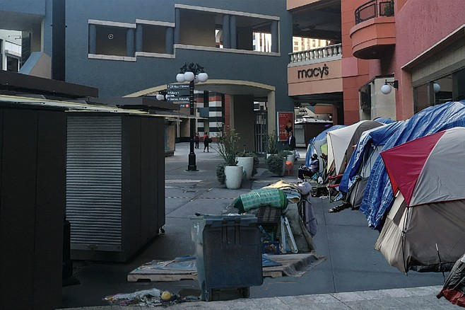 "Artist's rendering of Macy's future neighbors, should it fail to make way for proposed tech campus at Horton Plaza. ""Is this the kind of hobo chic that's good for the Macy's brand?"" asked Mayor Faulconer as he presented the image. ""Because we've got plenty here in San Diego, and we're happy to share."""