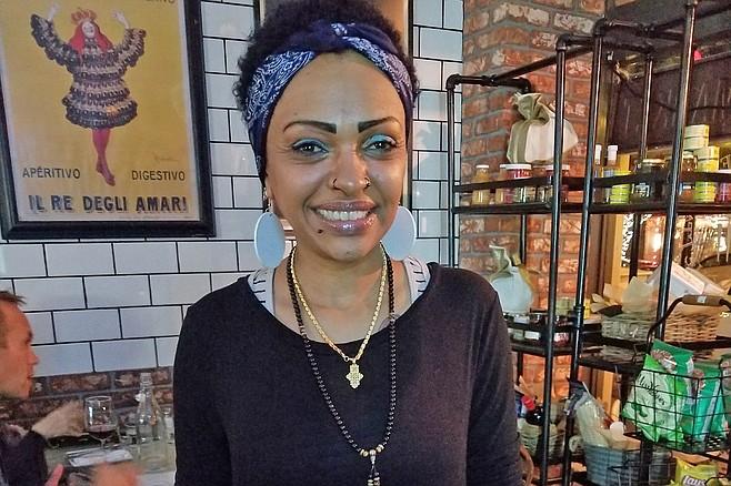 Samantha's electric blue eyeshadow brightens the dim-lit enoteca