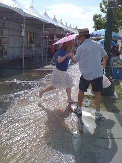 Woman crossing Date Street 'stream' during Artwalk.