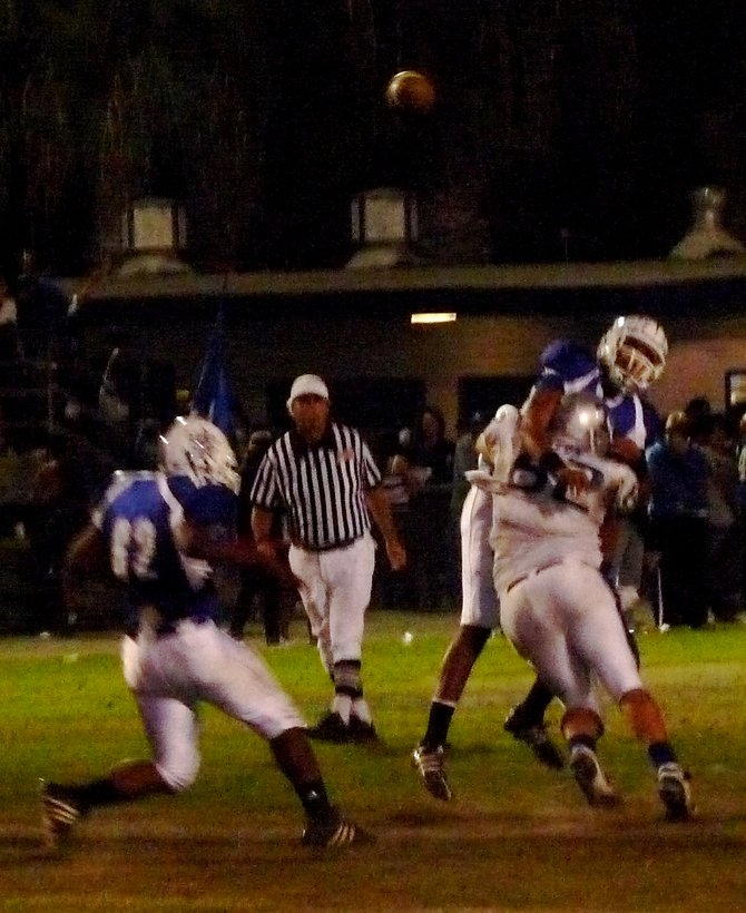 Chula Vista quarterback Victor Perez gets nailed by Eastlake defensive lineman Alex Baez after releasing the ball