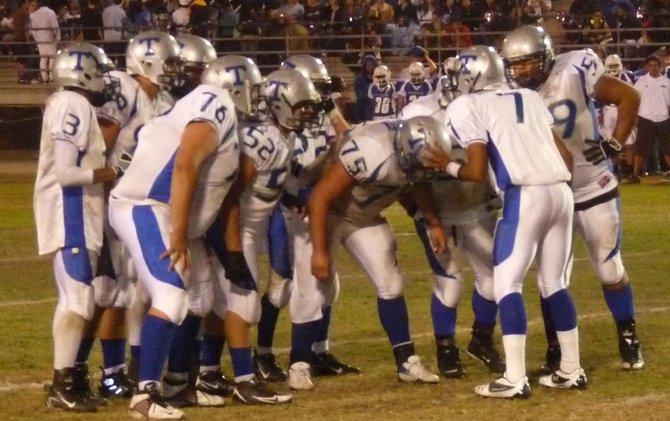 Eastlake quarterback DeAngelo Barksdale and the Titans offensive huddle