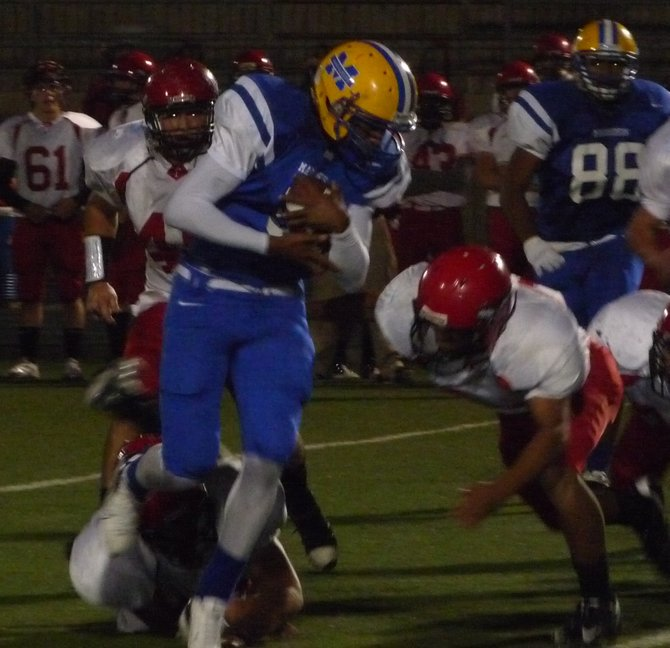 Mira Mesa quarterback Kevin Ozier covers the ball as he scrambles out of the pocket