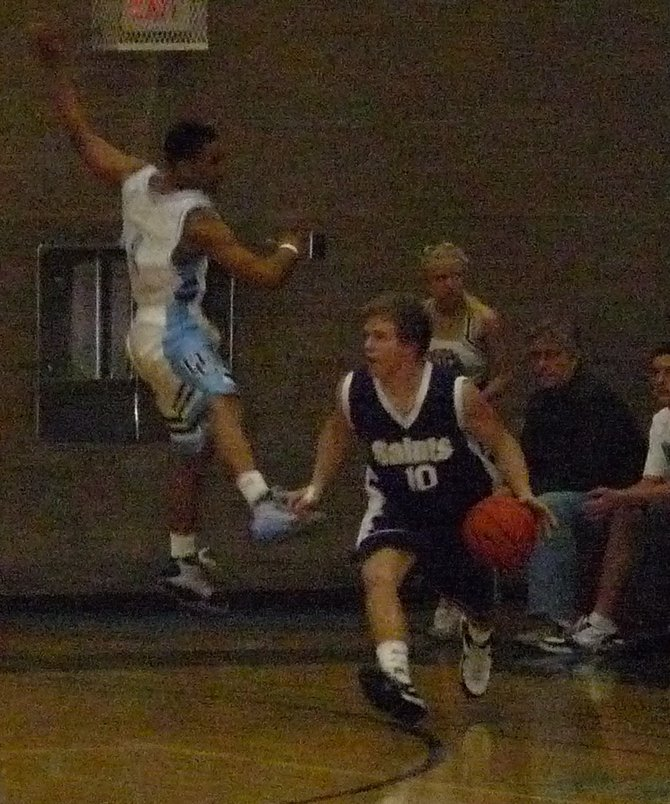 St. Augustine guard Cody Anderson dribbles under University City guard Mark Hills