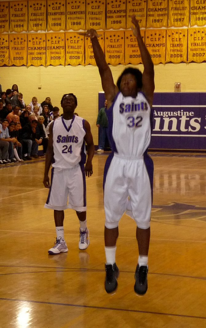 University City guard Mark Hills guarded by St. Augustine guard Kaum Brandon on the perimeter