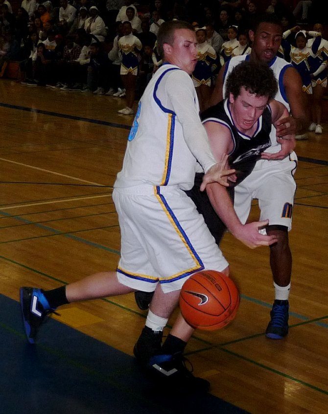 Carlsbad Charlie Parker fights for a loose ball against Mira Mesa forward Damon Williams and guard Kevin Ozier