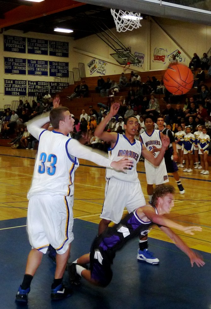 Carlsbad guard Sawyer Carlson takes the fall in the lane between two Mira Mesa defenders