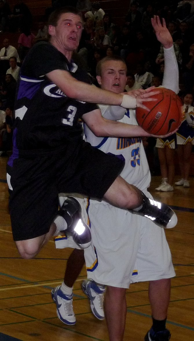 Carlsbad guard James Towner goes up for a layup in front of Mira Mesa forward Damon Williams