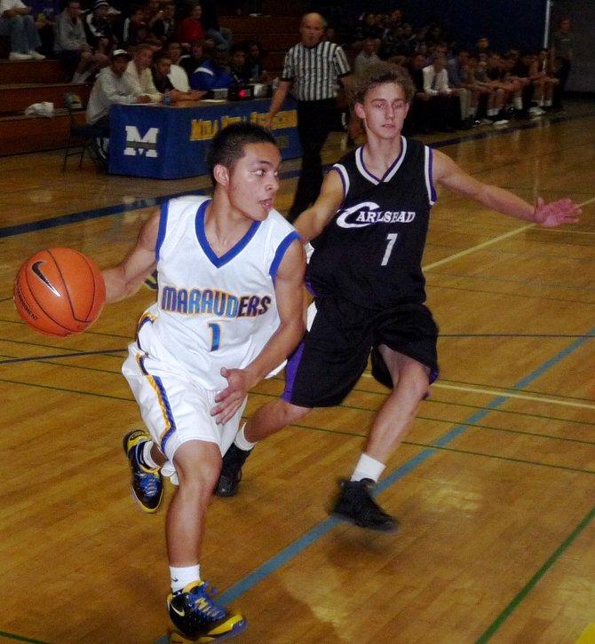 Mira Mesa guard Chris Mendoza gets around Carlsbad guard Sawyer Carlson