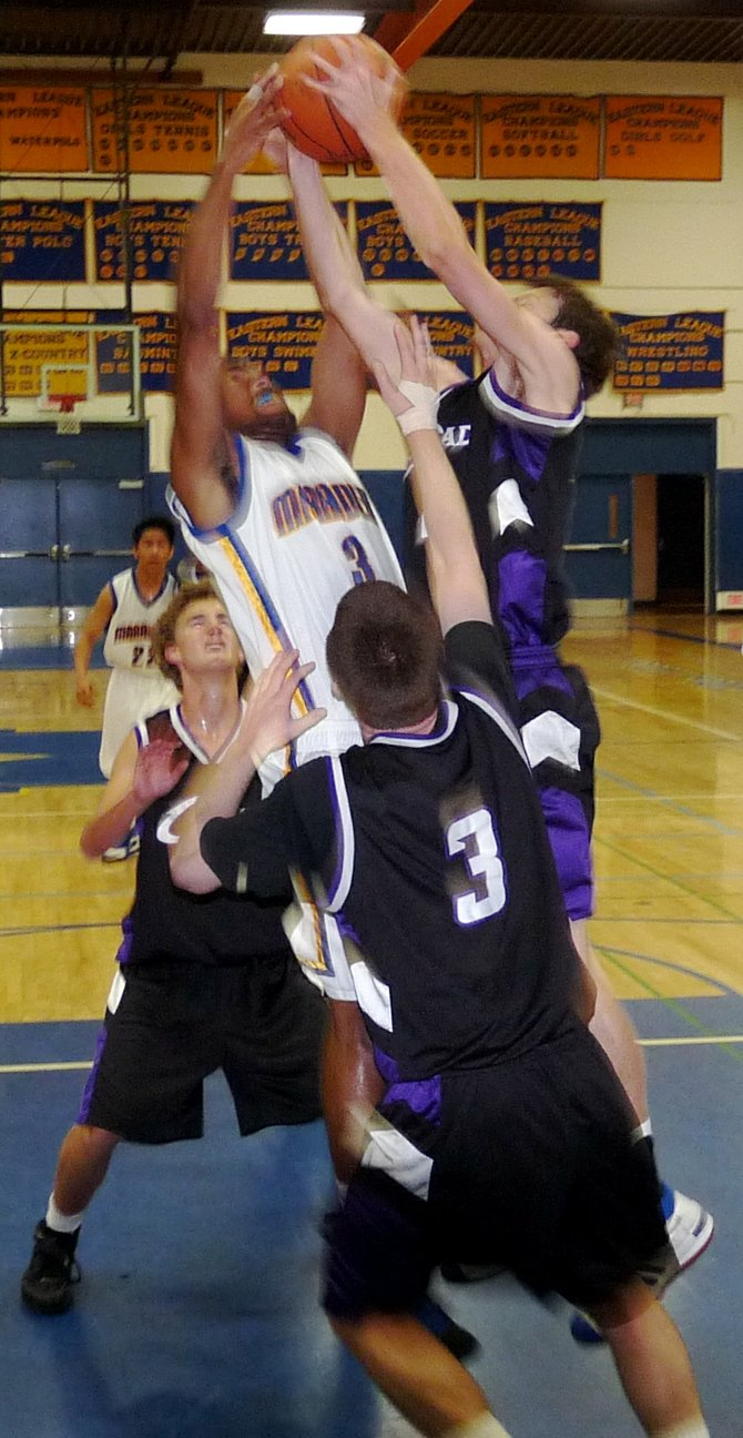 Mira Mesa guard Kevin Ozier and Carlsbad guard Cameron Burns fight for a rebound