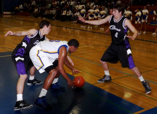 Mira Mesa guard Kevin Ozier tries to scoop up a loose ball between two Carlsbad defenders