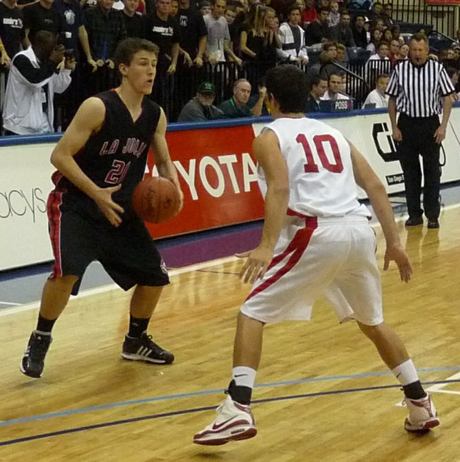 La Jolla forward Jack Latta guarded by Cathedral Catholic guard Chase Novak