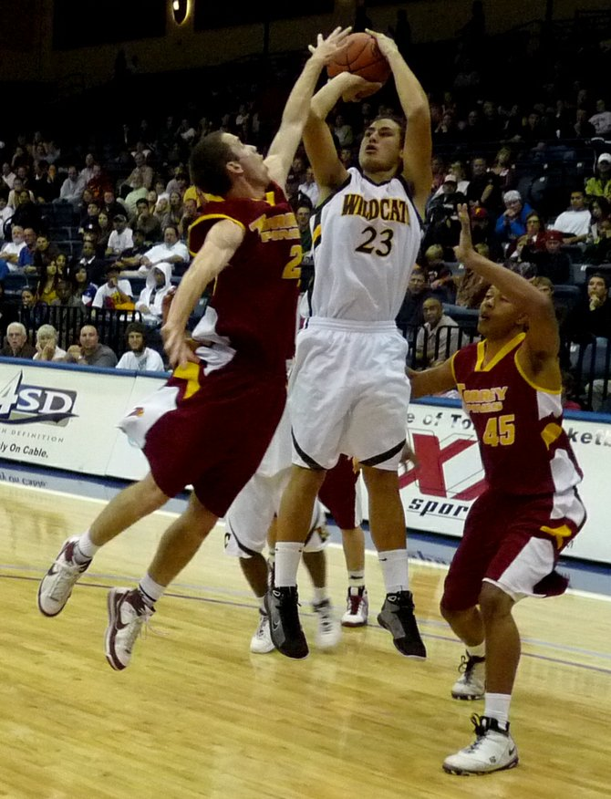 El Camino forward Ryan Ena shoots a jumper over an outstretched Torrey Pines