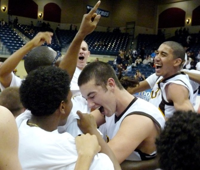 El Camino center Luke Evans (center) and the Wildcats celebrate their Division I title