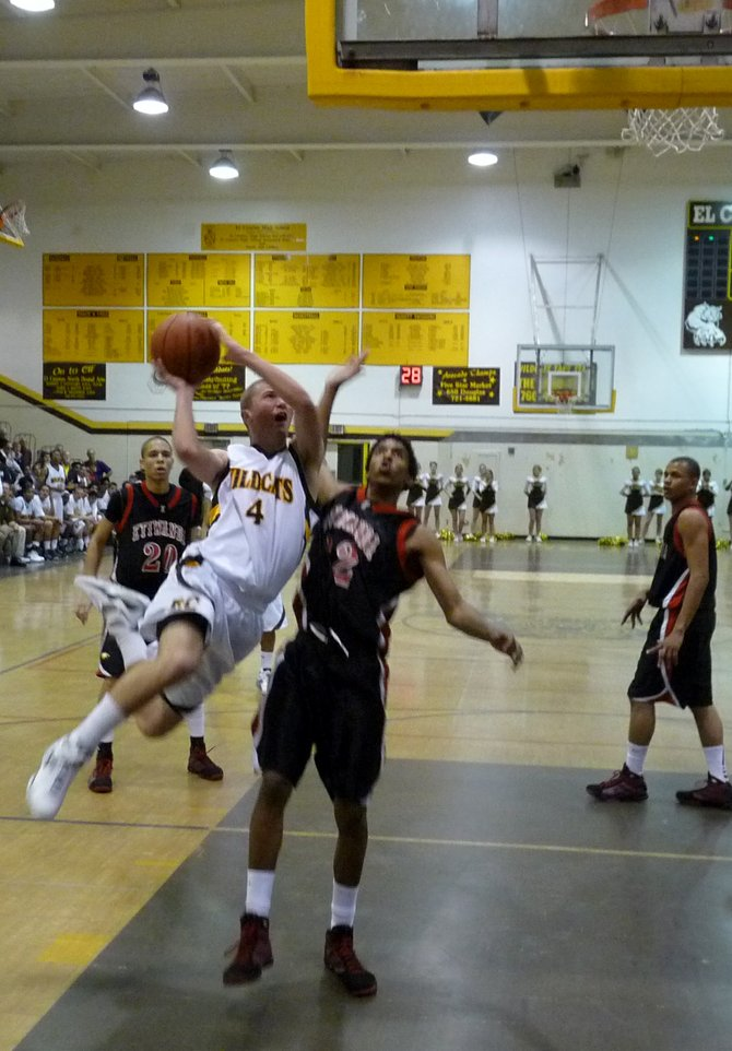 El Camino guard Griffin Hunter goes to the hole against Etiwanda guard Deronn Scott