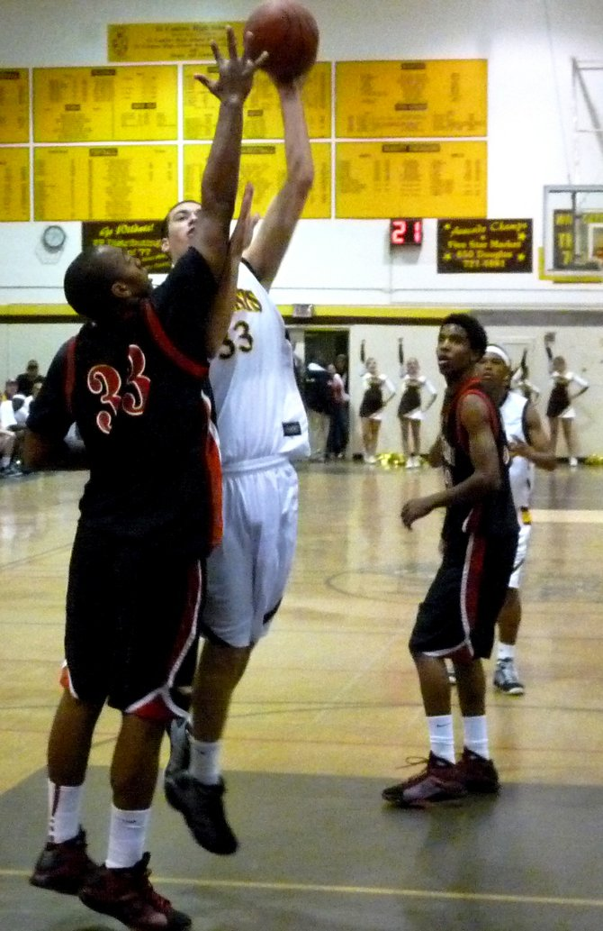 El Camino center Luke Evans puts up a one-handed shot against Etiwanda center Perris Blackwell