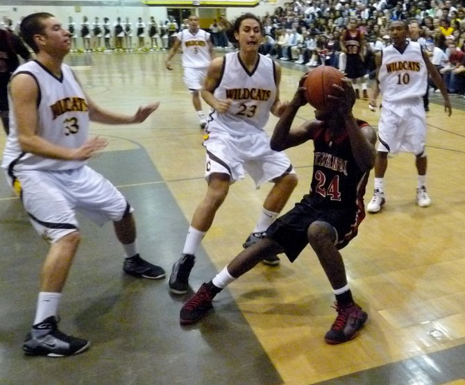 El Camino center Luke Evans (33) and forward Ryan Ena double-team Etiwanda forward Christian Katuala on the baseline
