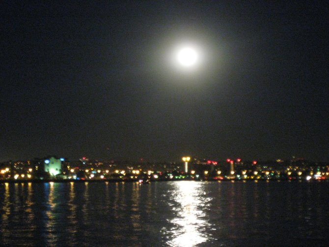 Shelter Island at night: The soft focus captures the full moon resting on the shoreline of lights still glowing