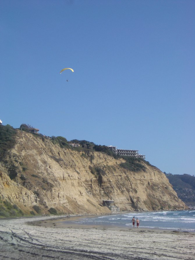 Paraglider sailing over beach walkers