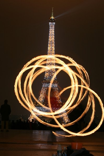 This is a photo of a fire dancer in Paris. The Eiffel Tower is lit up all spectacular like in the background. Absolutely fantastic.