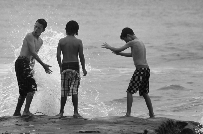 Three young friends catching waves in La Jolla.