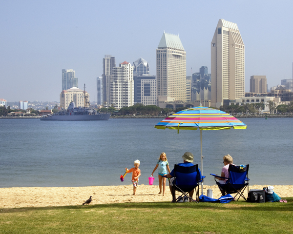 Two kids play in the sand watched by grandparents on a hot day. San Diego Downtown and navy ship in background.