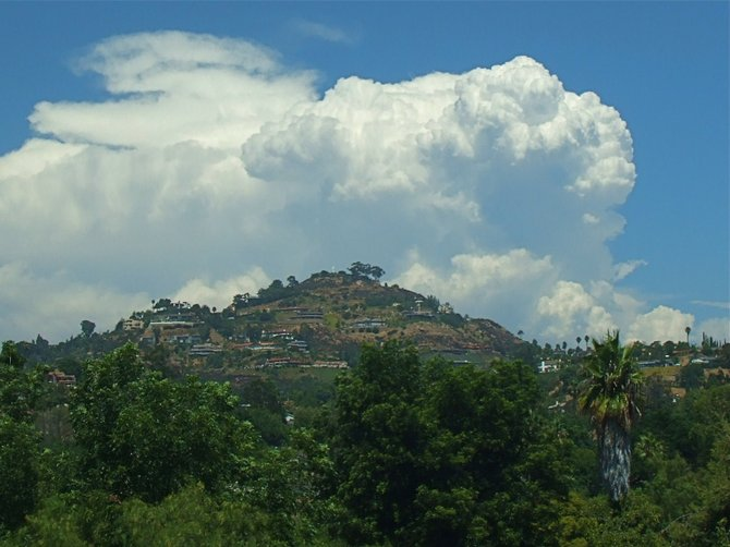 A photo of Mt. Helix with an East County Thunderhead in the background.