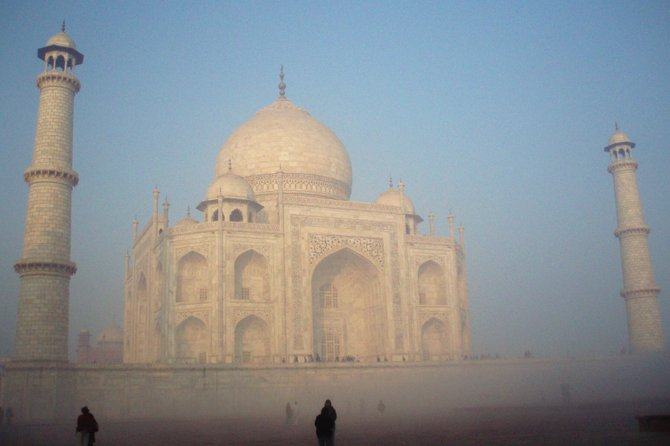 The Taj Mahal reveals itself after the morning mist burns away.