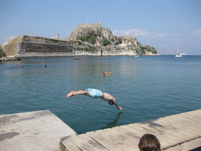 Municipal swimming in the Adriatic.  Diving, lounging, and playing water polo in the sea along the edge of the Grecian Island Corfu.  The Old Fortress sits up high in the background.  An iron bridge connects it to the present day town.