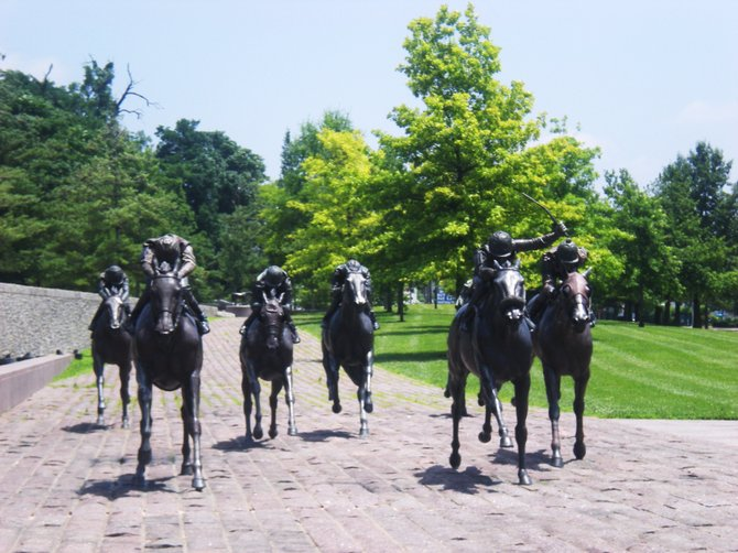"Lexington, known as ""Thoroughbred City"" and the ""Horse Capital of the World"", is located in the heart of Kentucky's Bluegrass region. Thoroughbred Park, a tribute to Lexington's horse industry, is home to these life-size sculptures of Thoroughbred horses. In front of a multi-jetted fountain, these seven life-sized bronze statues of jockeys astride racing horses rush towards an imaginary finish line.  On a berm behind the fountain stand grazing bronze horses and foals. A paved walkway through the park is dotted with bronze plaques memorializing notable people in the horse industry.  There is also a small bronze statue of ""Lexington"", the famous 19th century racehorse and a spectacular garden of red roses. This is a wonderful park to visit."