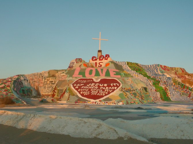 "I visited Salvation Mountain last month right before sunrise near Slab City, CA.  I reached my destination about three miles outside of town when I saw ""God Never Fails, Salvation Mountain."" I found the happy artist climbing a latter inside his creation in order to expand upon it. He explained that he thought the project would take 8 weeks, but it made him happy, so he stayed 27 years. He uses acrylic paint, left over tires and windows from the nearby junkyard and paints messages of God's universal love. He's one of the happiest people I've met and handed me a DVD and puzzle of his creation on my way out. Since 2002, it's been a national treasure and protected by the State."