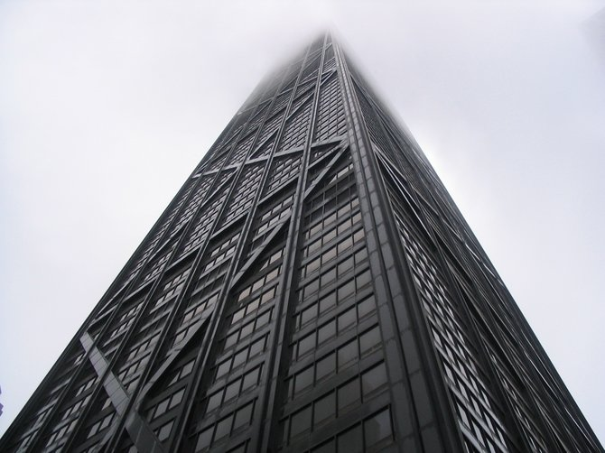 "Chicago's John Hancock Building reaching into the clouds! It is 100 stories and 1,127 ft. tall and houses offices, restaurants and about 700 condos. On ""The Signature Room on the 95th Floor"", patrons can look out at Chicago and Lake Michigan while they dine.  An annual stair climb race up the 94 floors from the Michigan Avenue level to the observation deck, called Hustle up the Hancock, is held on the last Sunday of February. The climb benefits the Respiratory Health Association of Metro Chicago: 2008 record time clocked at 9 minutes 38 seconds."