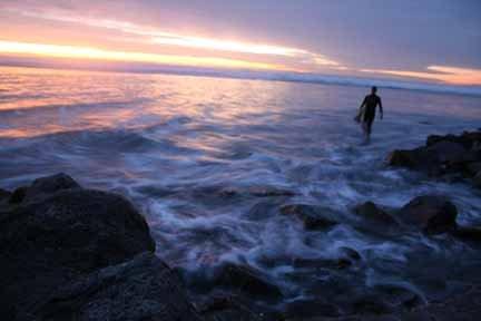 Surfer leaving during sunset