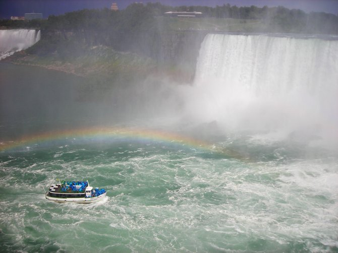 Maid of the Mist boat soaks into the basin of the Canadian Horseshoe Falls. Passengers are provided with raincoats (blue) to keep them dry from the mist.
