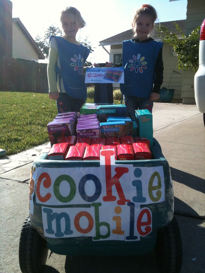 "Opening Day 2010 Girl Scout Cookie sales!  We loaded up the wagon and off we went around the neighborhood.  Zelly and Roxy Ford trying to earn another coveted ""patch"" to adorn their Daisy smock. Rather than taking orders and delivering the cookies a few week later, this year we just guess how many we can sell, place an order, than go for it!"