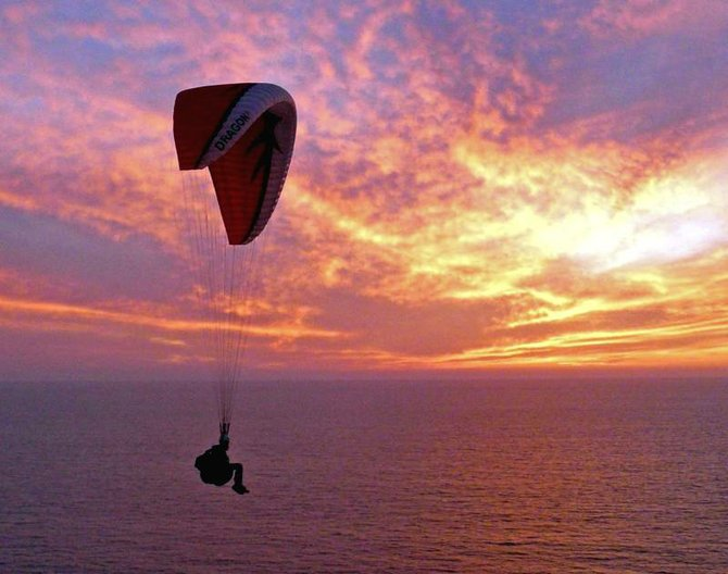 A paraglider at Torrey Pines gliderport enjoys one last ride as the sun sets.