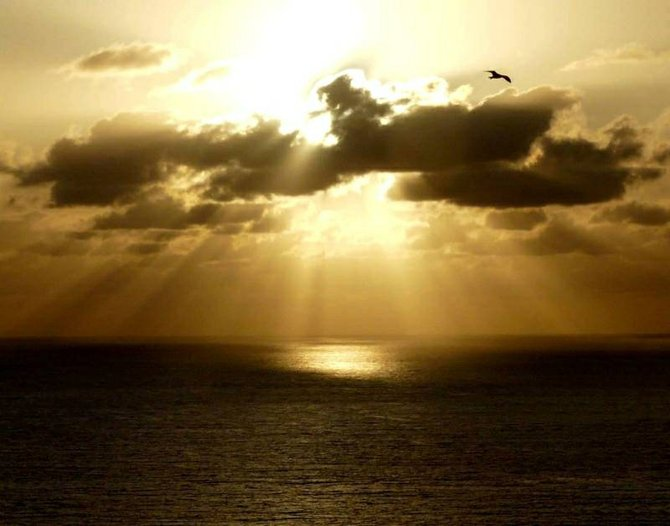 The sun breaks through the clouds bathing the sky and sea with golden sunbeams at La Jolla Shores.