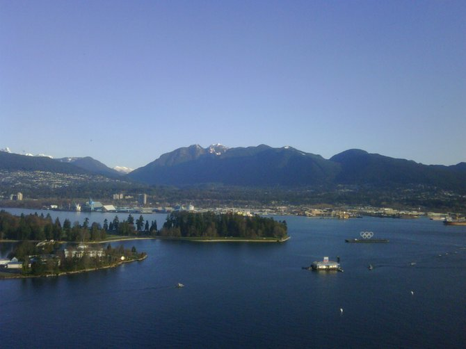 A view of Stanley Park and the North Shore mountains.  The 2010 Olympic rings are anchored in the water.  Taken from a commercial high-rise in Vancouver's Coal Harbour district.