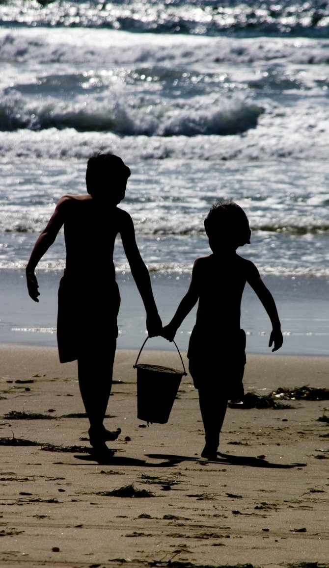 Mission Beach close to sunset (brothers sharing sand bucket)