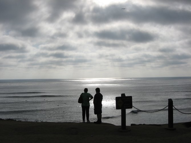 A couple staring out in to the ocean. From on top of the cliff- at Sunset Cliffs.