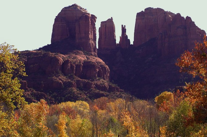 Fall foliage at sunet frames the the red rocks of Sedona.