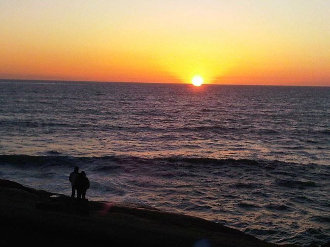 Two solace souls shares in a sinking sun at the Sunset Cliffs.