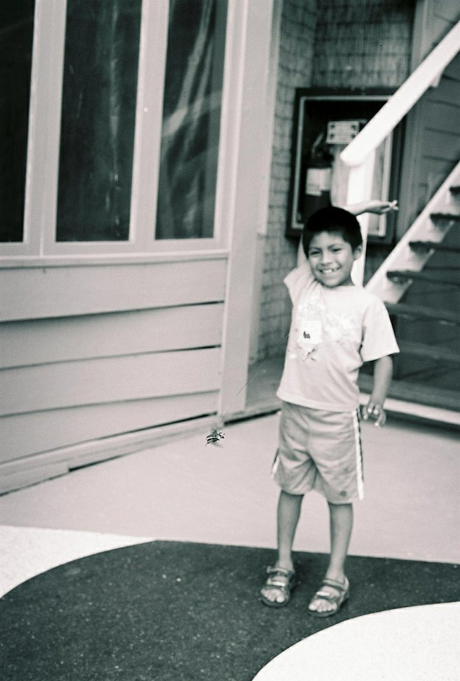 The shot was taking with 35mm black and white c41 Kodak film. ISO 400 The shot was of a little boy in Rosarito who had a June bug tied to a string. While the bug was in mid air I manage to take a shot of the June bug and the boy laughing.