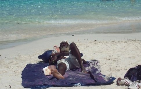 A local West Indian chills out on a hot day on Coki Beach, St. Thomas US Virgin Islands.