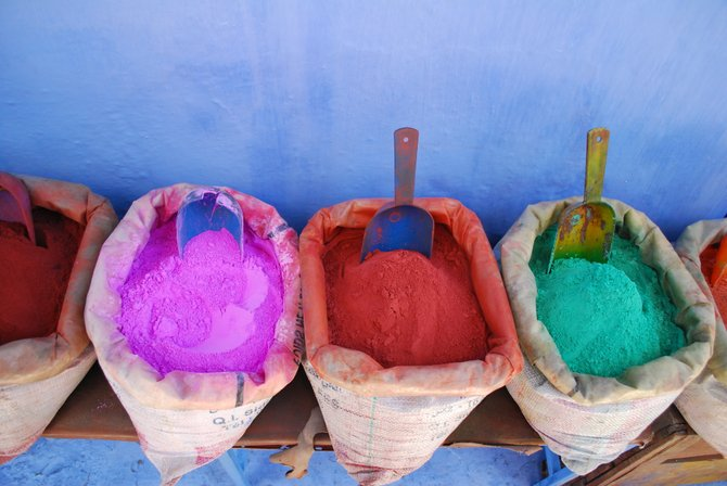 Vendor in Chefchaouen market, selling powdered fabric dye that will be used by Moroccan rug and textile makers.