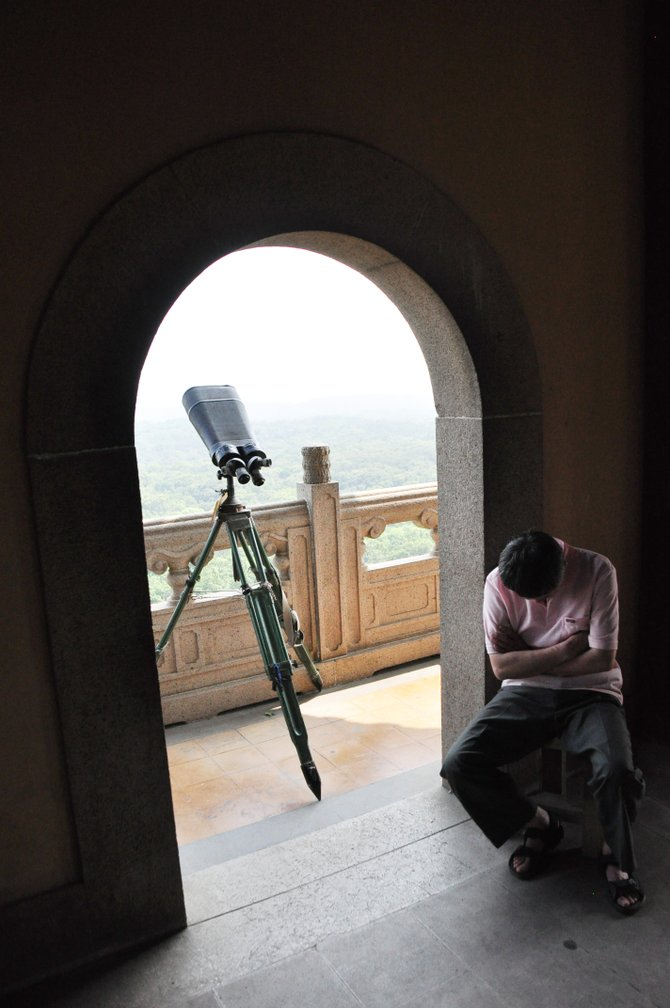 Local worker rents his binoculars at purple mountain. He's inside the highest traditional tower in south china, facing the inside of the tower, and sleeping.