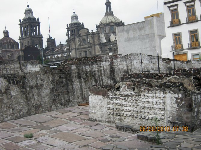 Ruins of the ancient Aztec capital, Tenochtitlan at the Templo Mayor in Mexico City. Notice the cathedral in the background and the skulls in the foreground.