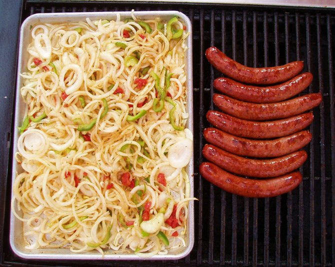 Sausauge links, peppers and onions on the grill at the San Diego County Fair.