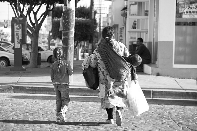 A little girl and her mother walking down the street