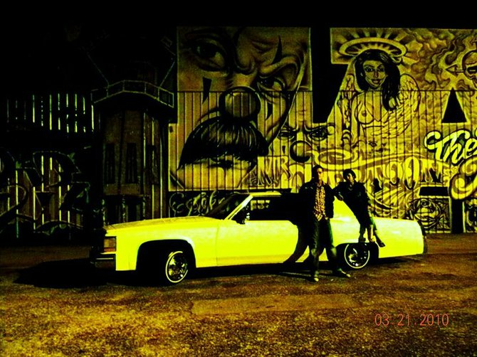 While riding around downtown L.A. visiting my dad and his girlfriend Amber, we stopped at this great wall of graffiti. They posed with the Cadillac.